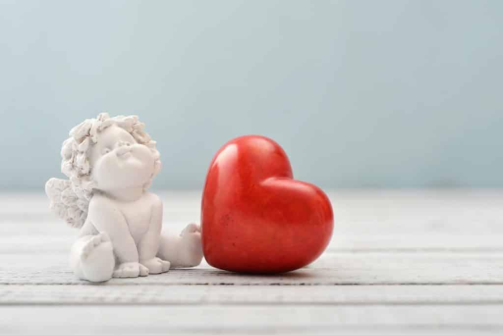 Imagem da estátua de um anjinho do amor e ao lado dela um coração de cera na cor vermelha.