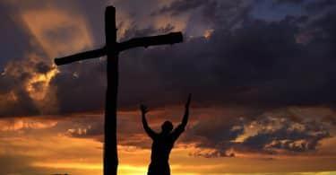 Silhueta de homem agachado próximo de uma cruz. Ao fundo, cenário de pôr do sol.