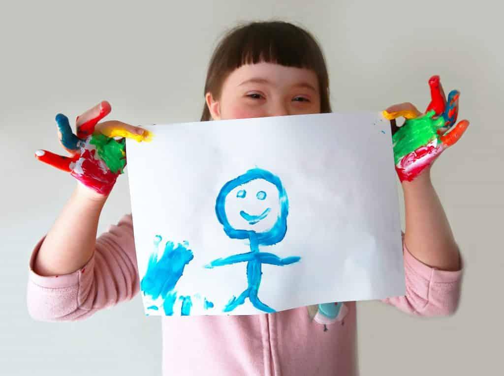 Imagem de uma criança portadora da síndrome de down. Ela está com as duas mãos coloridas com tinta e está segurando uma folha branca com um desenho de um menino feito de caneta na cor zul.