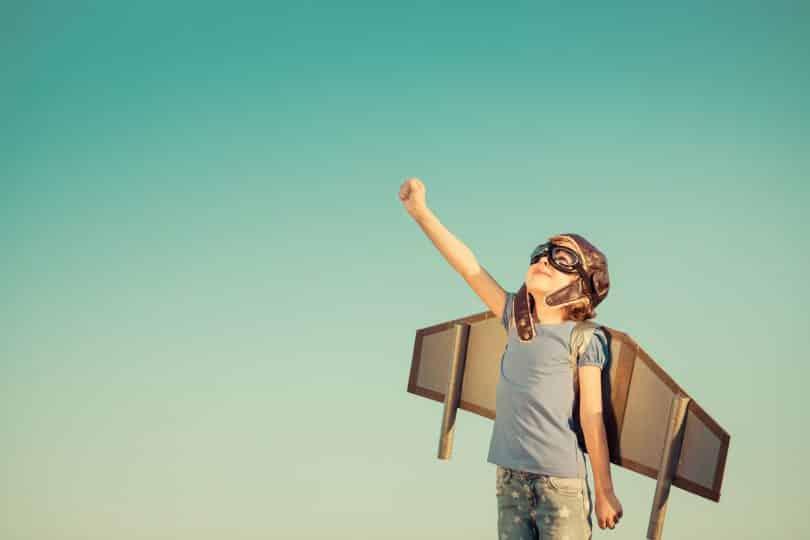 Criança feliz brincando com asas de brinquedo em fundo de céu de verão.