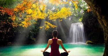 Mulher jovem em pose de ioga sentada perto de cachoeira