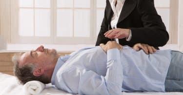 Homem branco deitado numa maca com mão em cima.