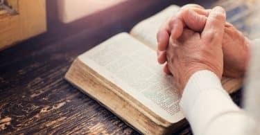 Mulher segurando uma Bíblia nas mãos e orando