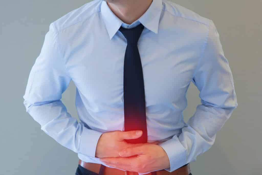 Homem branco com roupas sociais e mãos na barriga, em sinal de dor.