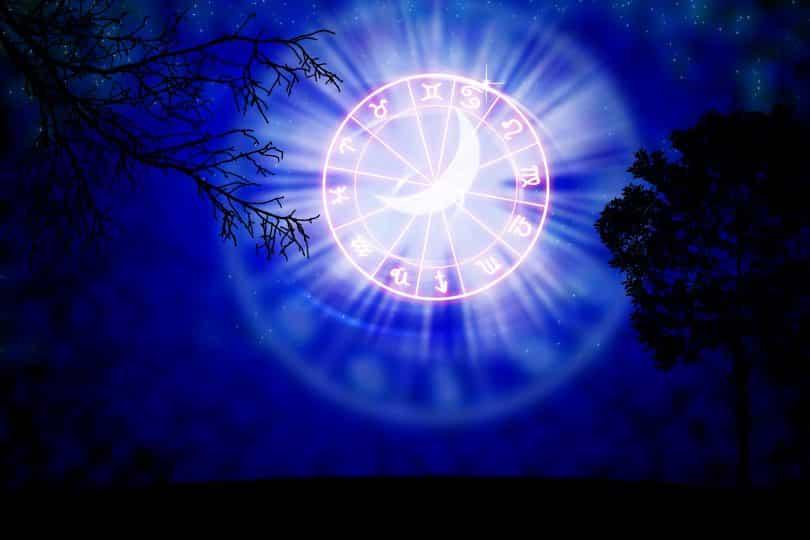 Imagem noturna de um lindo céu com uma lua bem bonita sobre o mapa astral trazendo os 12 signos do zodíaco.