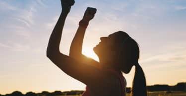 Mulher levantando os braços para comemorar o sucesso