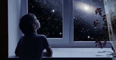 Menino olhando o Universo pela janela