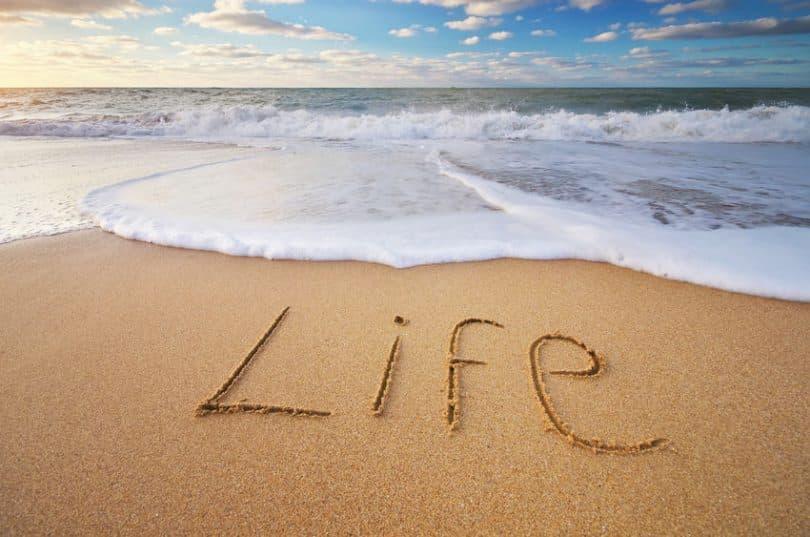 """Palavra """"Life"""" (vida em inglês) escrita na areia"""