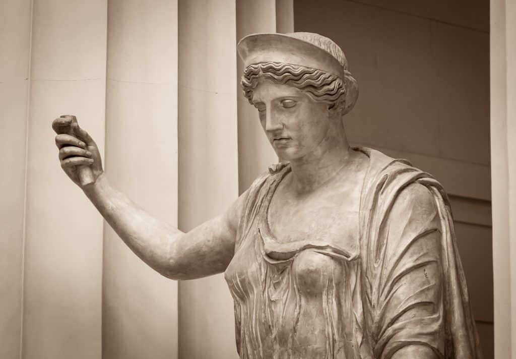 Imagem da estátua de uma mulher representando a deusa Hera. Em uma das mãos ela segura um objeto.