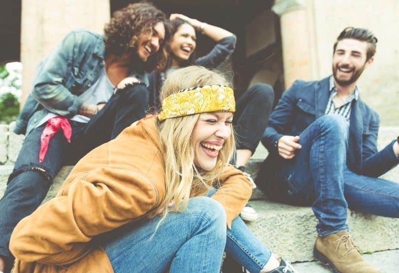 Grupo de quatro amigos rindo ao ar livre.