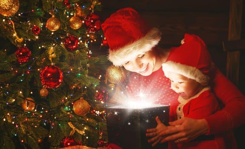 Mãe e filho bebê com um presente mágico da árvore de Natal