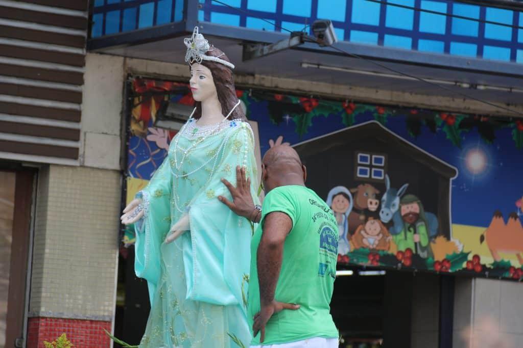 Imagem da estátua de Iemanjá no meio de uma rua. Ao lado dela, um filho de santo usando uma camiseta verde. Ele está com uma de suas mãos sobre ela.