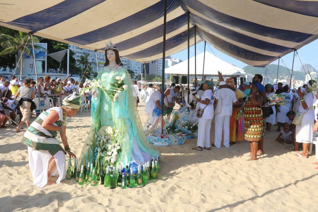 Imagem da estátua de Iemanjá embaixo de uma tenda na areia. Uma filha de santo faz homenagens à ela colocando varias garrafas de champanhe e flores brancas.