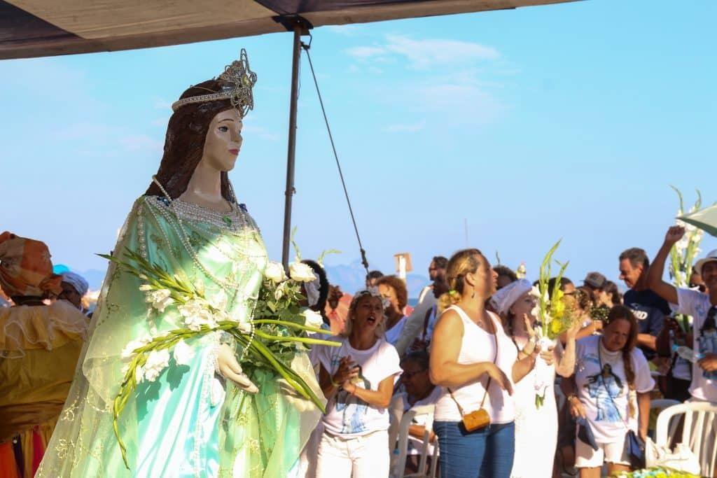Imagem da estátua de Iemanjá na praia. Ao lado vários devotos dela cantando e fazendo oferendas como flores.
