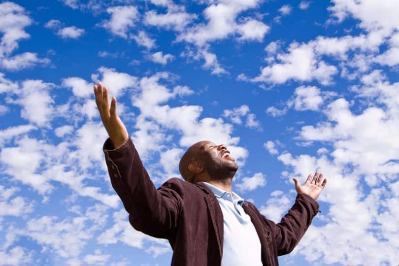 Homem feliz estendendo as mãos para o céu