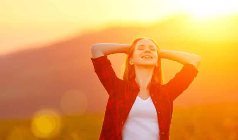 Mulher sorrindo com os braços erguidos em um cenário externo.