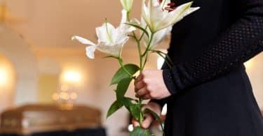 Imagem de uma mulher vestindo uma roupa preta dentro de uma sala de velório. Ela está segurando um ramo de flor branca e está ao lado do caixão.