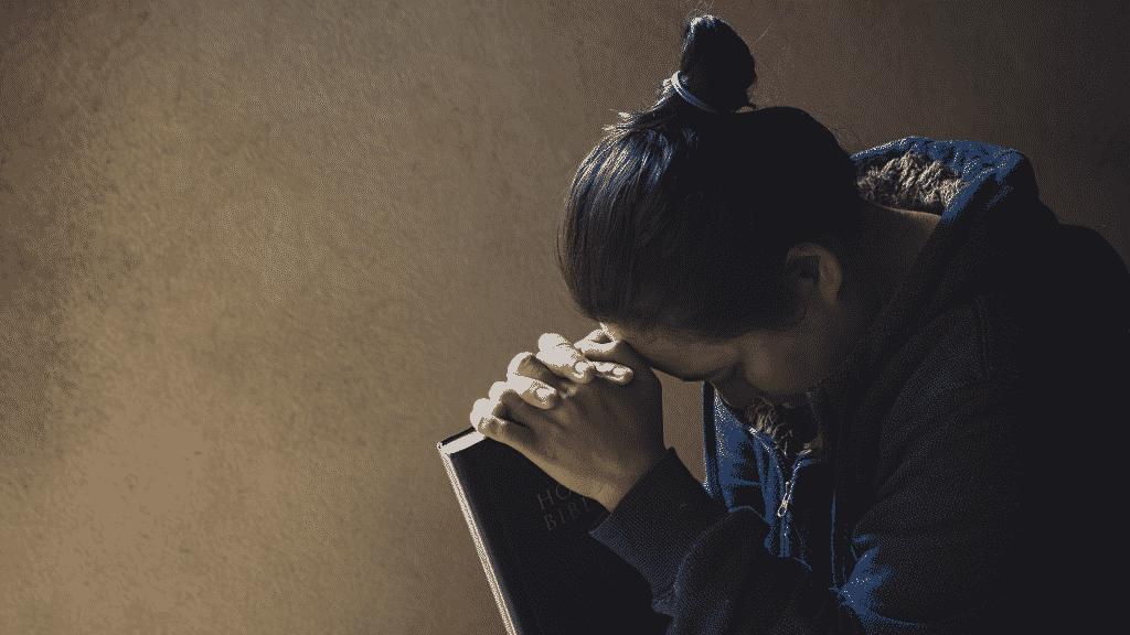 Pessoa orando de olhos fechados enquanto segura a bíblia