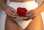 Mulher usando roupa de baixo branca segurando a flor vermelha em um copo menstrual