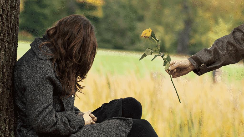Pessoa oferecendo uma flor amarela como pedido desculpas para mulher cabisbaixa