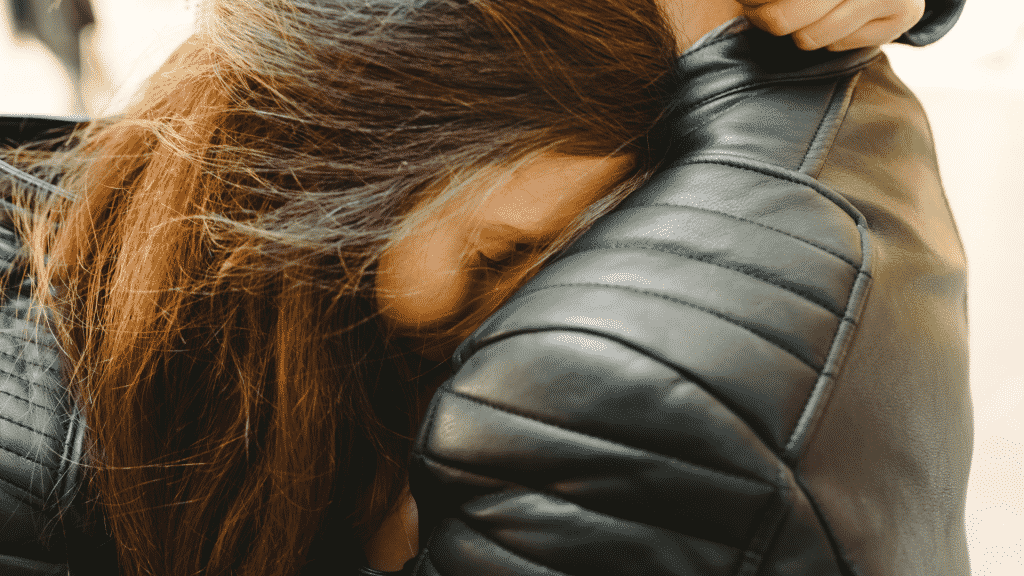 Mulher de olhos fechados encostada no ombro de um homem