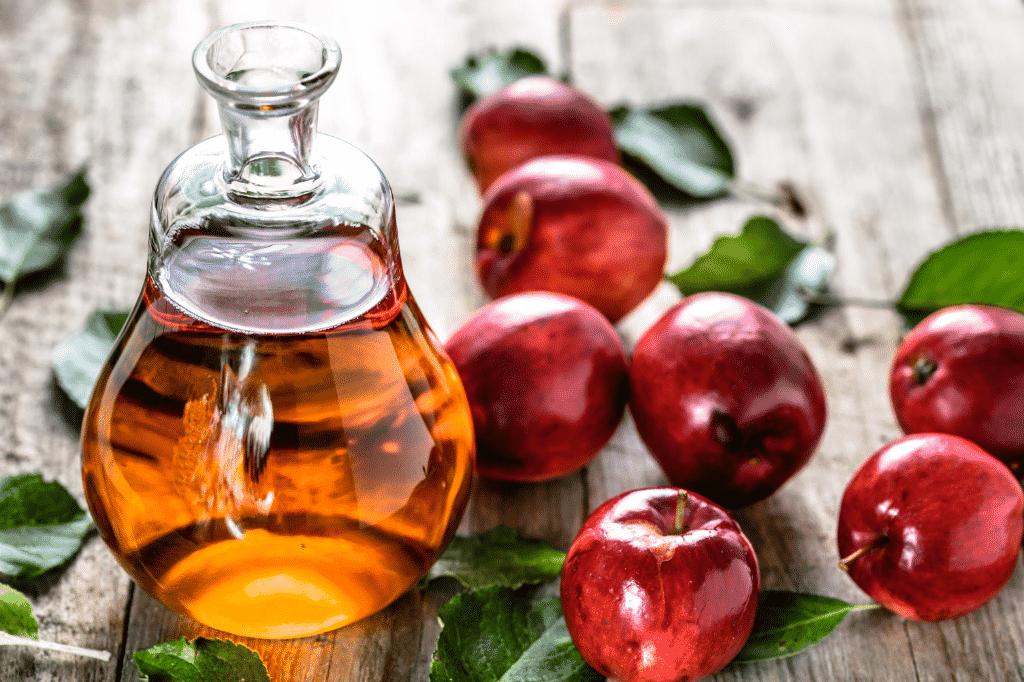 Vinagre de maçã ao lado de maçãs sobre mesa.