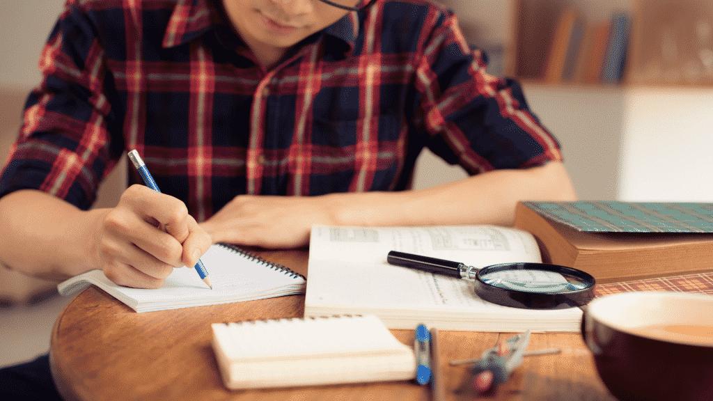 Garoto estudando e escrevendo anotações com livros em lupa sobre a mesa