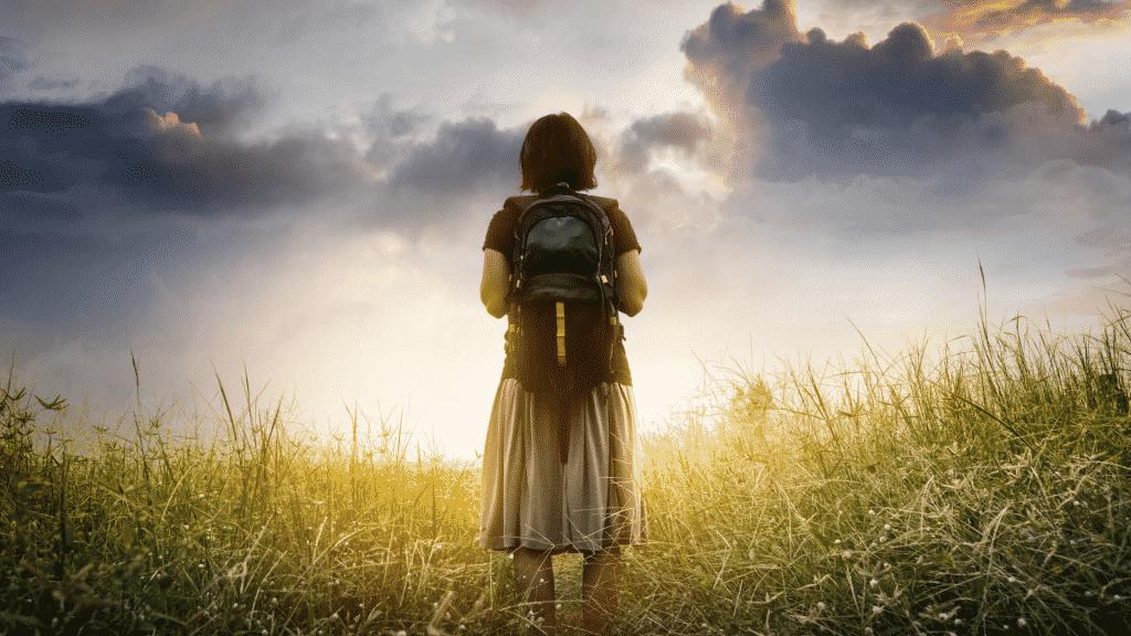 Menina em um campo com mochila na costa