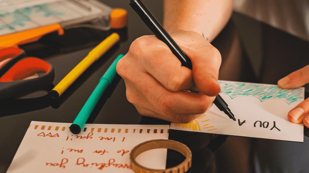 Pessoa escrevendo em um papel com lápis coloridos