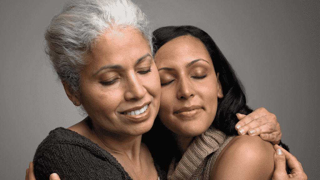 Mãe e filha se abraçando.