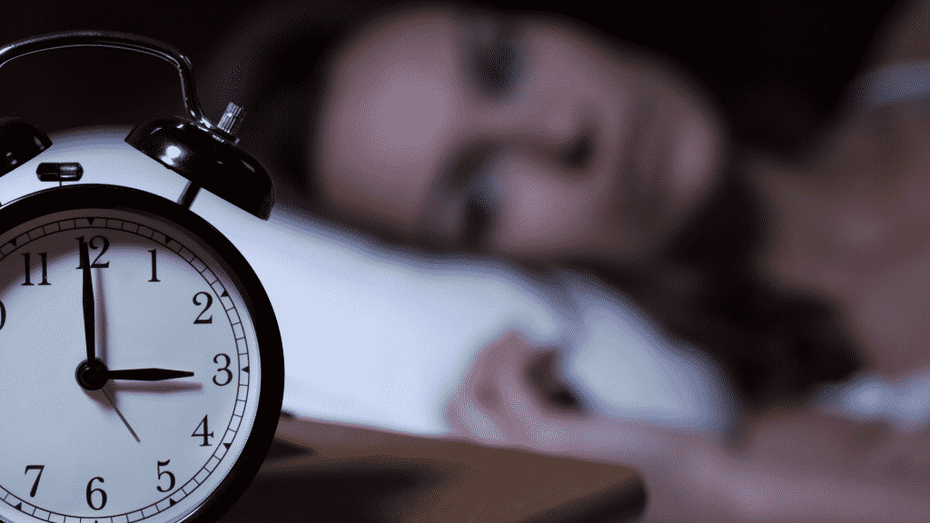 Mulher acordada e relógio marcando 3 horas da manhã