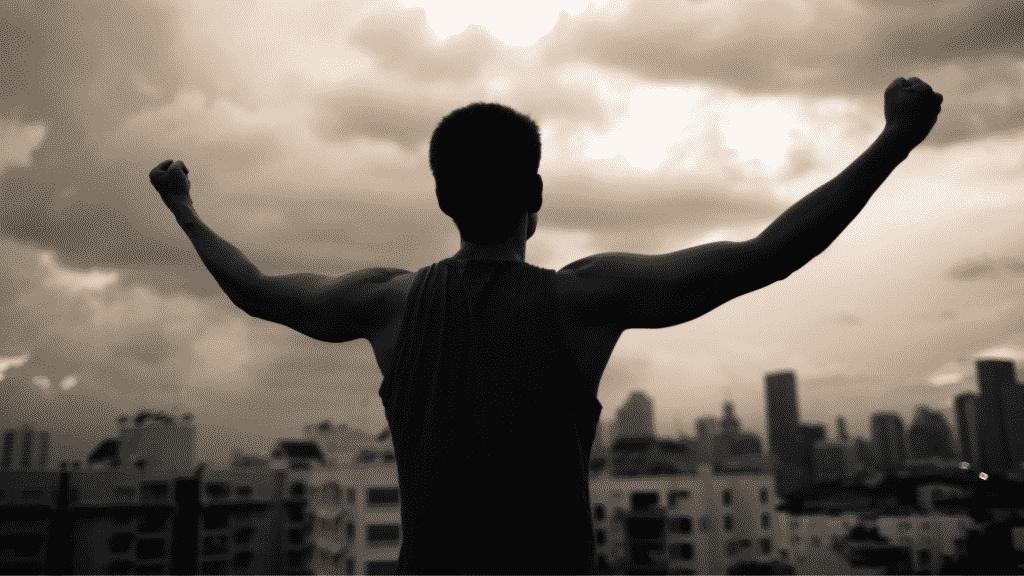Homem com braços abertos e punhos cerrados olhando para o céu