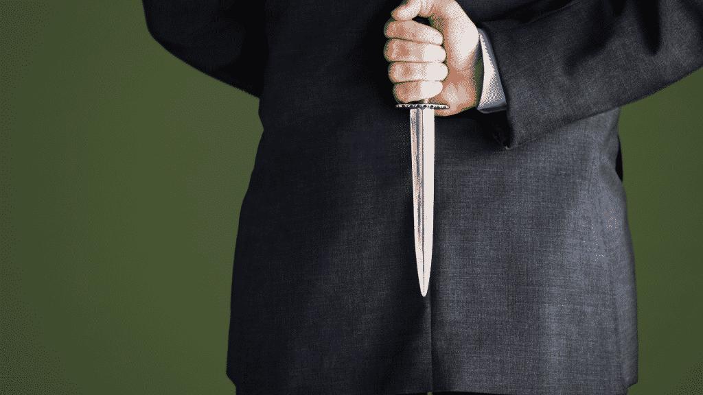 Homem segurando uma faca nas costas