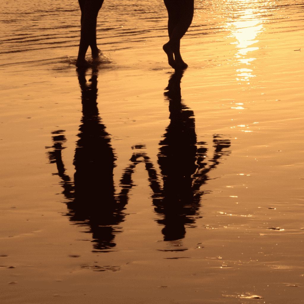 Reflexo na água de duas pessoas andando na praia juntas