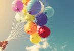 Pessoa segurando vários balões coloridos