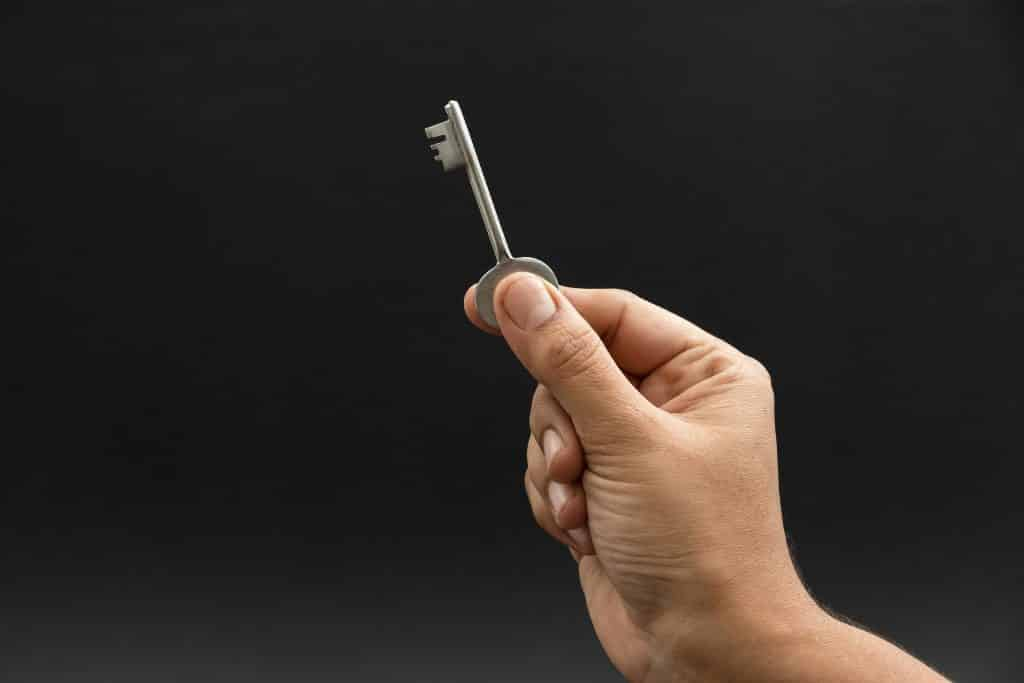 Imagem de uma mão segurando uma chave.