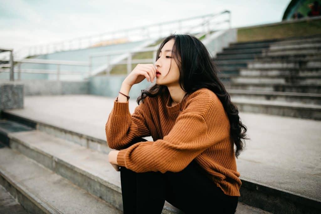 Mulher asiática sentada numa escada com mão apoiada no joelho levada à boca.