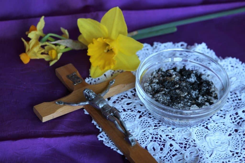 Imagem de uma mesa forrada com toalha roxa e sobre ela uma toalha pequena branca de renda, um pote de vidro com cinza, um crucifixo e uma flor amarela.