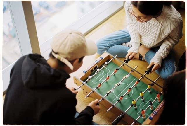 Homem e mulher brancos jogando mini pebolim.
