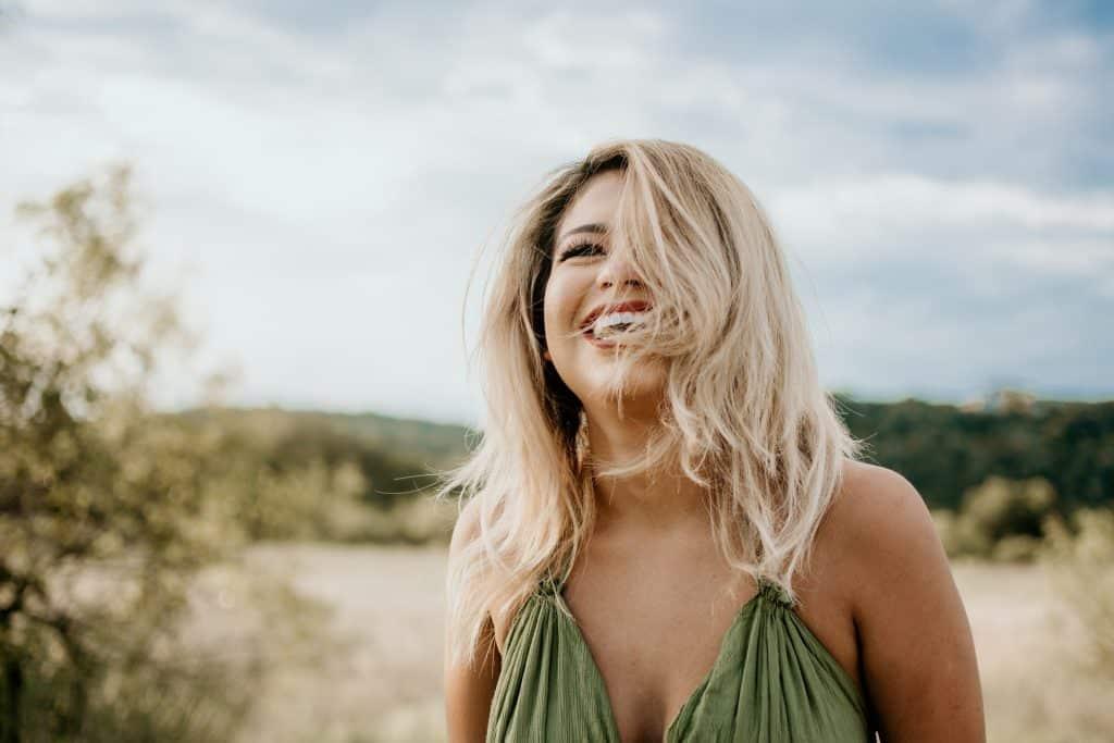 Mulher branca de cabelos curtos e loiros ao vento, com expressão sorridente.