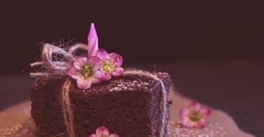 Imagem de um pedaço de brownie de chocolate disposto sobre uma travessa. Ele está decorado com um laço e um flor cor de rosa.