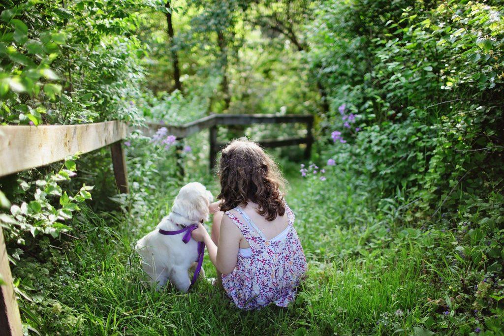 Imagem de um jardim com muito verde e de uma criança usando um vestido florido sentada na grama ao lado de um lindo cachorrinho branco.