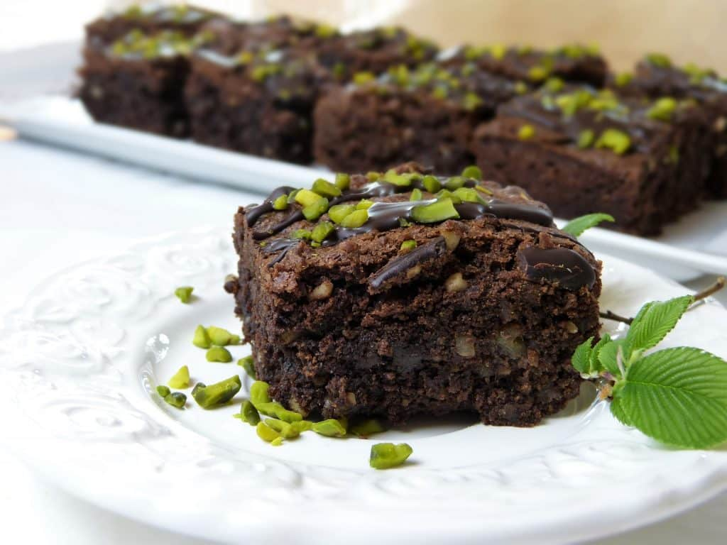 Imagem de um prato e uma travessa de porcelana branco e neles pedaços de brownie de chocolate sem glúten decorados com folhas de hortelã.