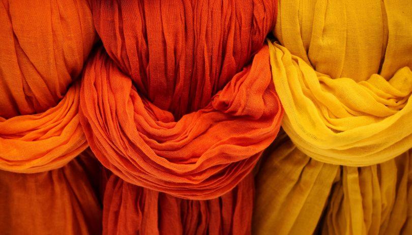 Imagem de três tecidos nas cores laranja claro, laranja avermelhado e amarelo para serem utilizados para hamonizar o ambiente.