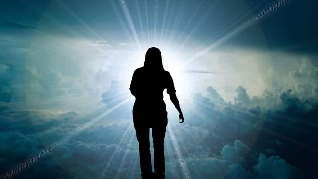 Imagem de uma mulher andando próximo às nuvens em direção ao céu.