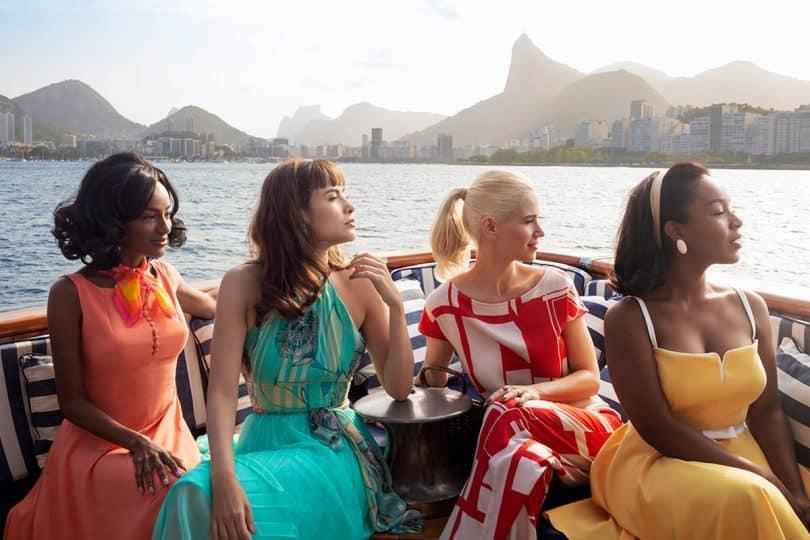 Quatro mulheres, sendo duas brancas e duas negras, sentadas num barco olhando para o lado.