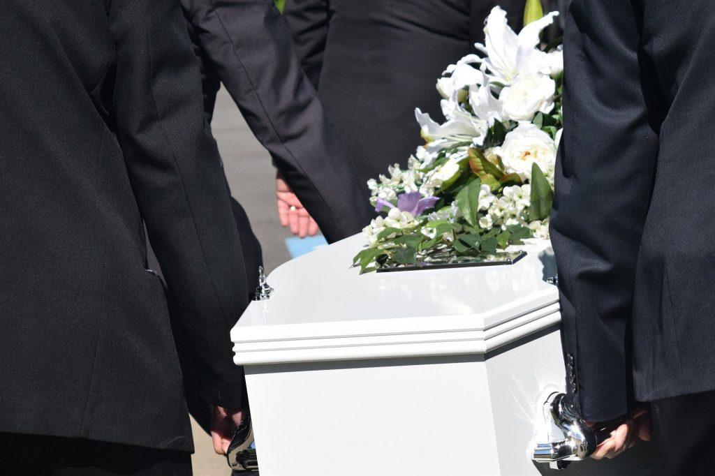 Imagem de algumas pessoas usando um terno preto carregando um caixão branco que acabou de sair do velório. As pessoas estão levando o caixão para o túmulo onde o corpo será enterrado.