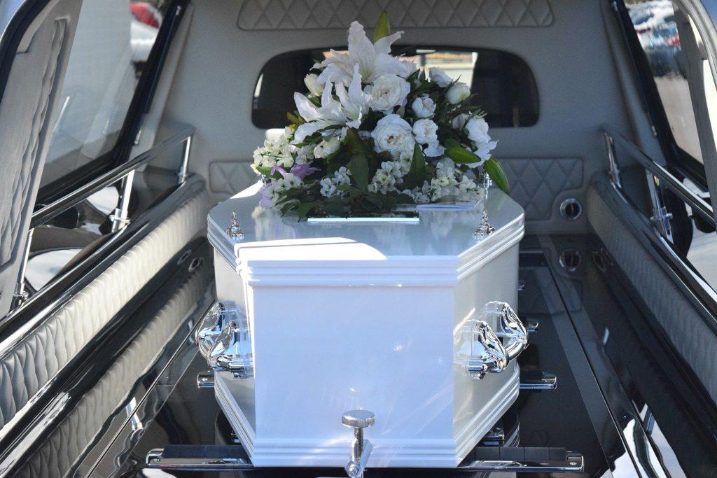 Imagem de um carro funeral e dentro dele um caixão branco com uma coroa de flores sobre ele. O carro está trazendo o corpo de uma pessoa para o velório.