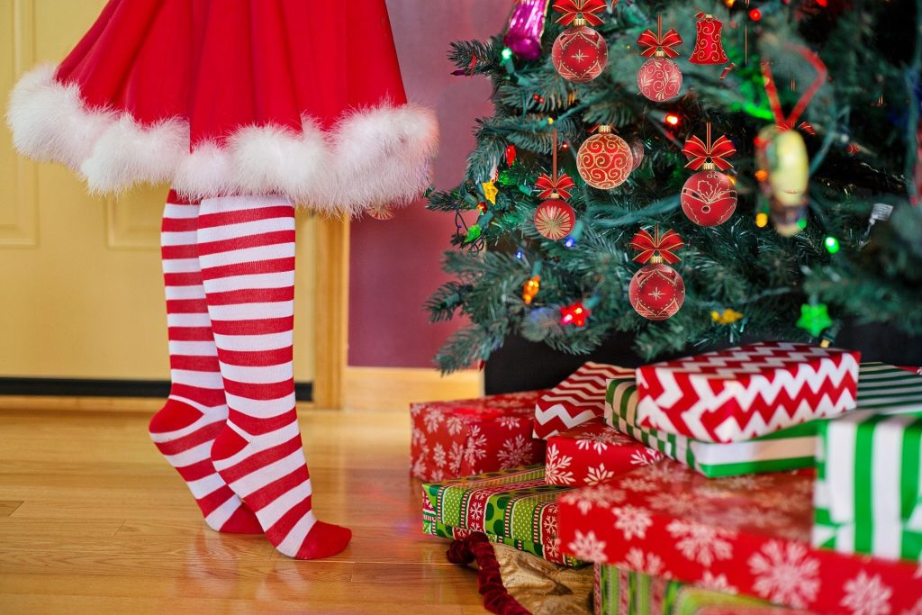 Imagem de uma mulher decorando a árvore de natal. Ela usa uma saia vermelha com pompom branco na barra e uma meia listrada nas cores vermelho e branco.