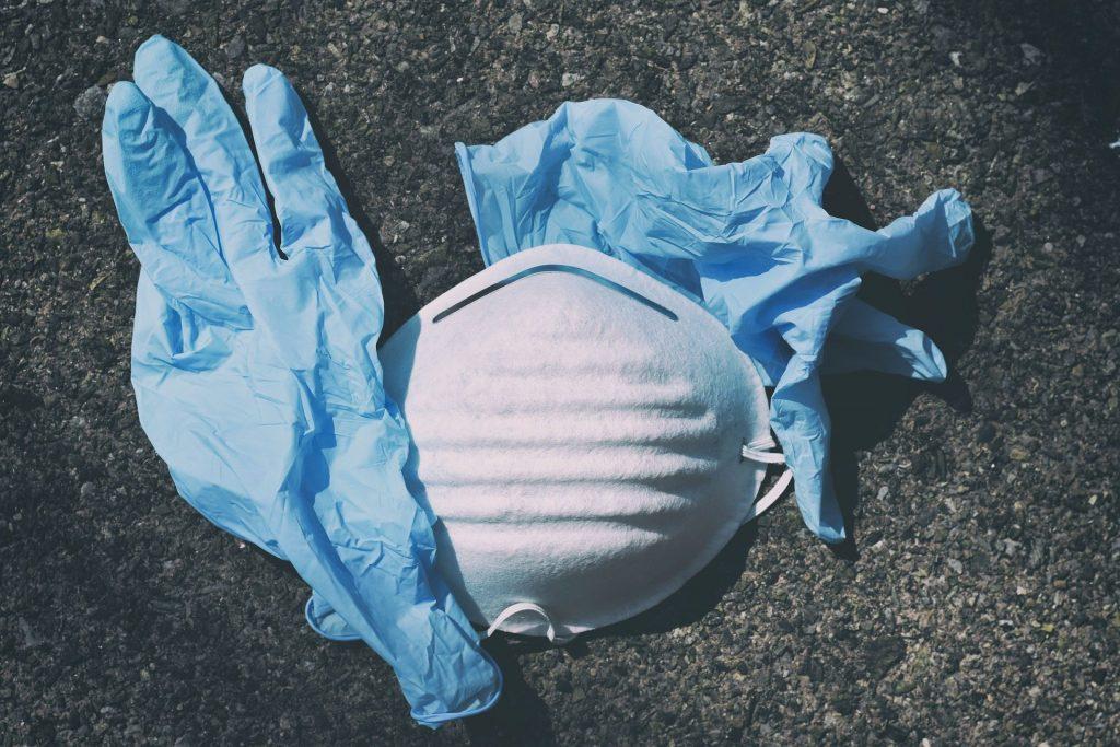 Imagem de uma máscara de proteção facial contra o Covid-19. Ao lado dela, duas luvas plásticas na cor azul.